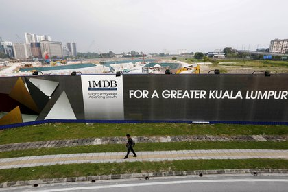 El hombre va a la cartelera Malasia Development Berhad (1MDB) 1 para el desarrollo de los fondos de Tun Razak Exchange en Kuala Lumpur.  REUTERS / Olivia Harris / Foto de archivo: