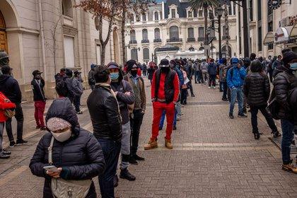 Con máscaras protectoras, la gente se reúne frente a la oficina de una administradora de fondos de pensiones en Santiago, Chile.