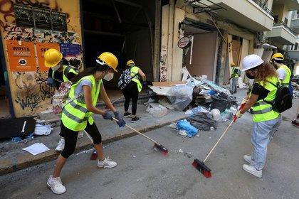Voluntarios limpian escombros en la calle después de una explosión cerca del puerto libanés de Beirut (foto de REUTERS / Aziz Taher)