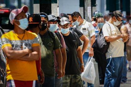 Para protegerse del coronavirus, un grupo de personas con mascarillas va a donar alimentos durante la epidemia de coronavirus el 23 de junio de 2020 en el distrito Corona de Queens, Nueva York.  (Foto AP / John Minchillo)