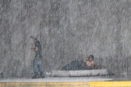 Dos residentes de la calle se refugian de la lluvia en Central Avenue en Monterey, México.  EFE / Mar & # 237;  una Julia Casta & # 241;  eda: