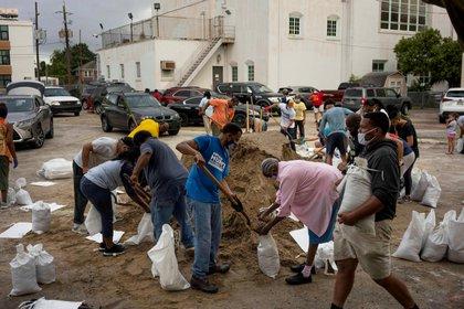 La gente llena sacos de arena en la iglesia de St. Raymond, donados por el alcalde de Latoya Cantelli, Louisiana, Nueva Orleans el 25 de agosto de 2020.  REUTERS / Kathleen Flynn / Foto de archivo: