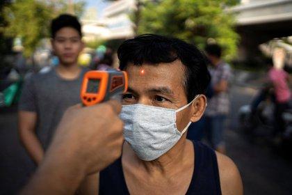 Un hombre con una máscara de coronavirus usa una máscara en un templo en Bangkok, Tailandia (REUTERS / Athit Perawongmetha)